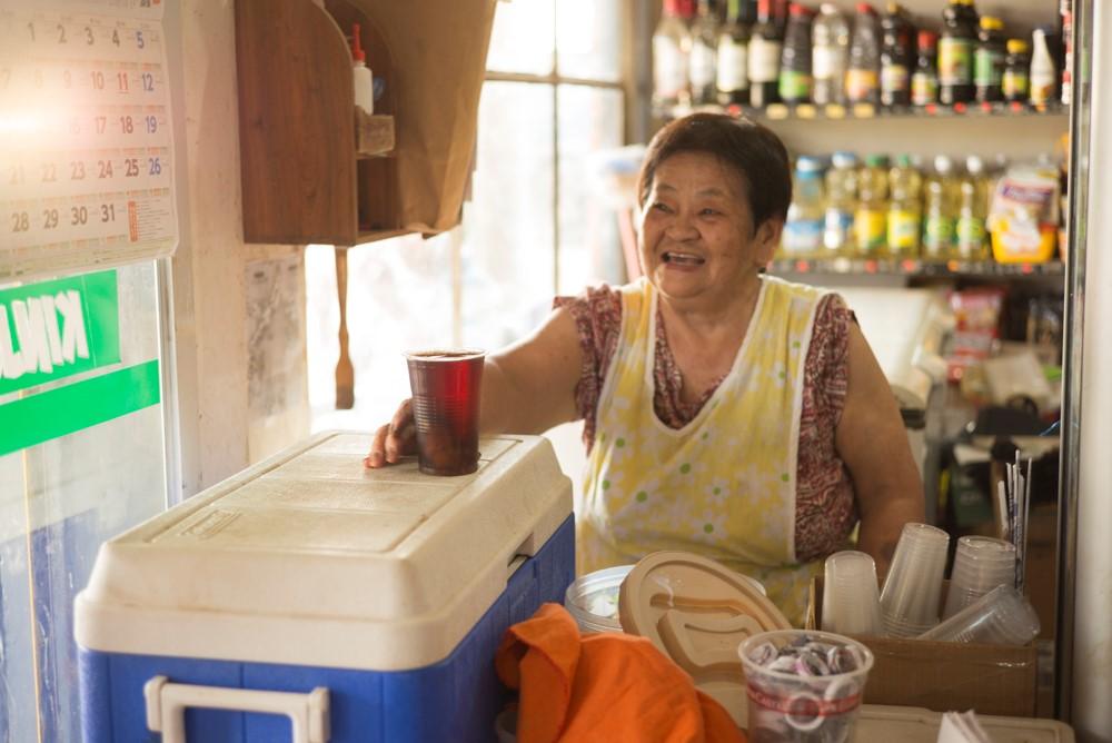 干し桃のジュース、モコチンチを持つオキナワ村のおばさん