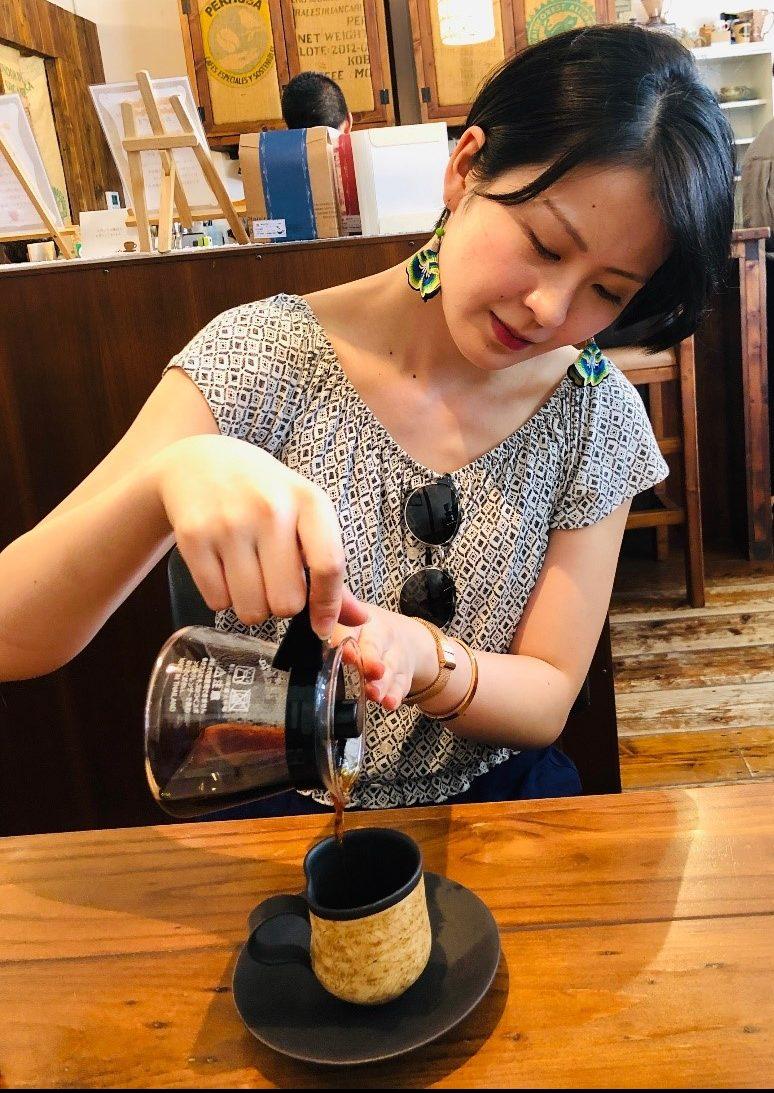 貴重な沖縄産コーヒーをカップに注ぐ滝田さん